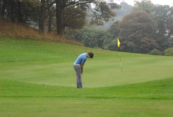 A Gibson putting towards flag on green